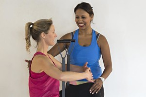 Amy helps client with Pilates exercise