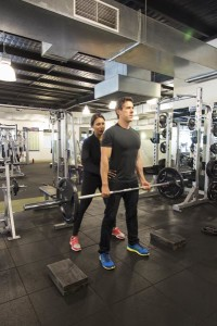 Amy helps client lifting weights during personal training session